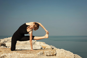 Wall Mural - Beautiful woman practicing yoga at seashore