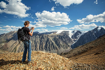 Man in travel in the mountains make photo on mobile phone