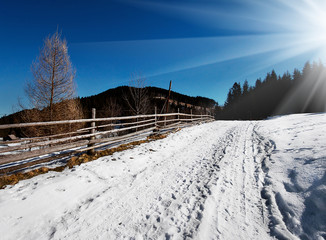 Snow-covered path along the wooden fence