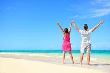 Wall Mural - Happy free couple cheering on beach travel holiday