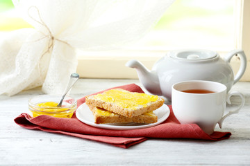 Toasts with honey on plate and cup of tea on light background