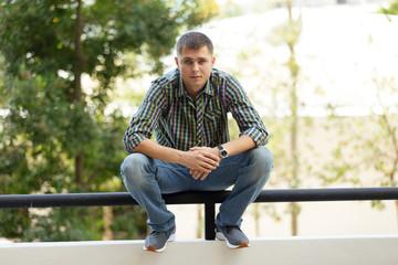 Man squatting on a ledge