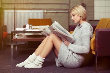 entspannte junge frau liest die tageszeitung