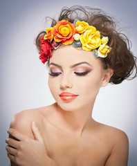Portrait of beautiful girl in studio with red and yellow roses