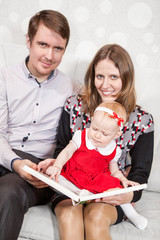 Father and mother sitting with baby girl trying to read a book