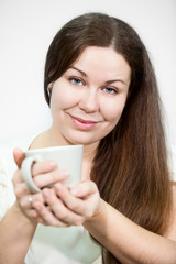 Caucasian happy smile woman holds tea mug in hands, background