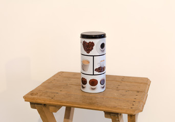 Coffee container with pictures on it, sitting on a wooden table