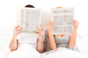 Couple in a bed reading newspaper