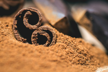 Cinnamon sticks with chocolate on vintage wooden background