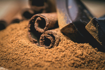 Cinnamon sticks with chocolate on wooden background