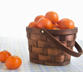 Fresh oranges in a basket on a table