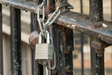 A Lock and chain on Rusty Metal Fence
