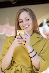 Happy young woman reading a message on the phone