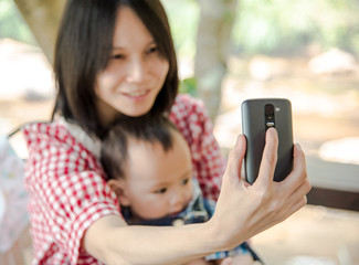 mother hold baby in arm taking selfie photo together