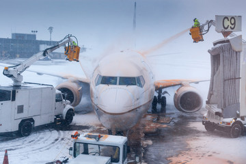 Airport attendant washing airplane in winter weather at an