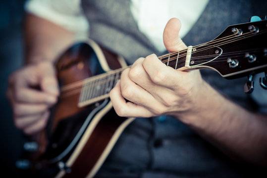 close up hands hipster man playing mandolin