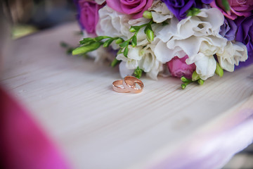 wedding rings and bouquet on the table