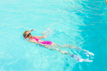 little girl snorkeling in swimming pool