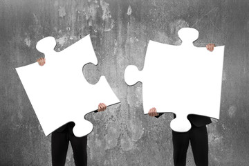 Two business people assembling white jigsaw puzzles with concret