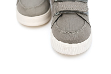 front of pair of grey shoes on a white background