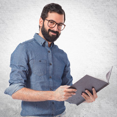 Happy hipster man reading a book