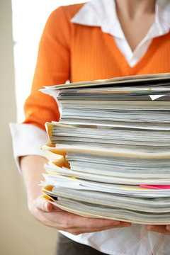 woman in grey holding stack of folders