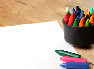 Oil pastel crayons in a mug on a wooden table