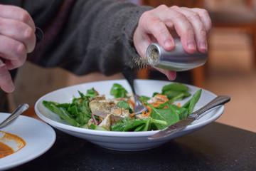 Man seasoning his salad