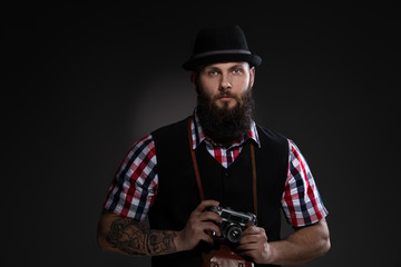 Bearded man in a hat holding an old camera
