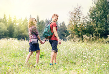Young couple on the walk in summer forest