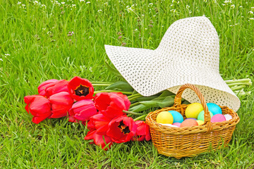 Basket with Easter eggs, tulips and hat
