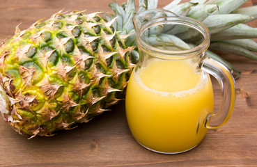 Pineapple juice of pot on wooden table