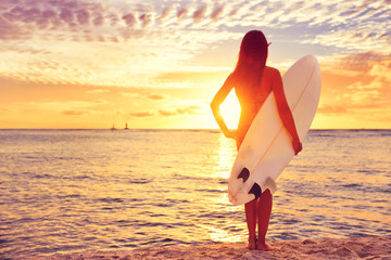 Surfer girl surfing looking at ocean beach sunset