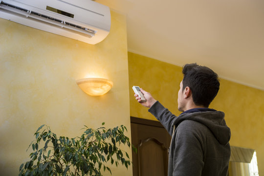 Young man switching on the air conditioner