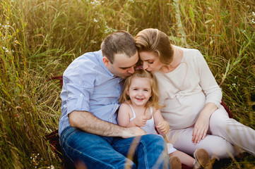 Родители целуют маленькую дочь