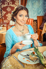 Girl in vintage dress in the restaurant.