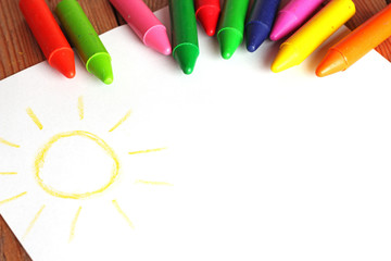 Crayons lying on a paper with painted children's drawing