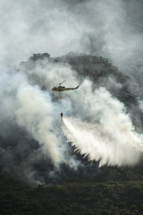 Fire fighting helicopter dropping water on a fire