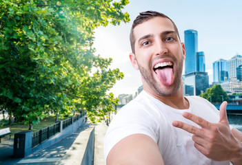 Happy young man taking a selfie photo in Melbourne, Australia