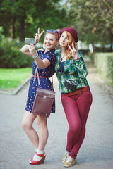 Two hipster girls with braces taking pictures of themselves on m
