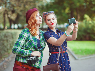 Two beautiful hipster girls taking pictures of themselves on mob