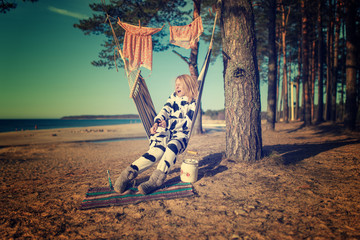 woman in cow pajamas in a hammock