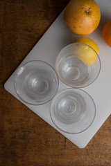 Empty glasses and fruits on white board
