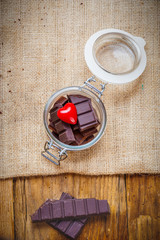 Chocolate and heart in a jar on a wooden background on the day o