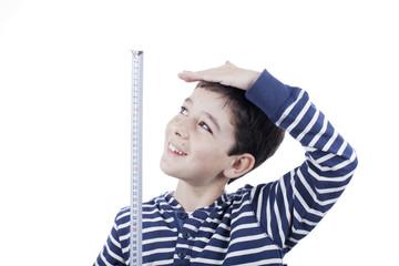 Niño midiéndose con un metro