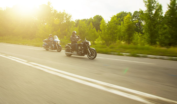 slow motion, two bikers riding unknown motorbike with blur movem