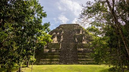 Young Women Climbing Mayan ruins at Tikal, National Park. Travel