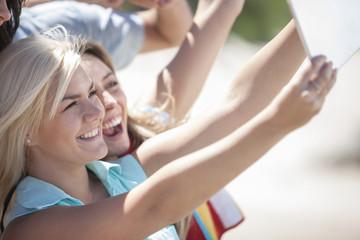 Freunde, die ein Selfie mit Tablet-PC machen, am Strand