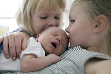 Zwei kleine Mädchen küssen ihren neugeborenen Bruder
