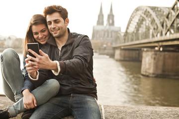 Deutschland, Köln, junges Paar macht  Selfie vor dem Kölner Dom